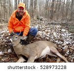 Small photo of Wisconsin deer hunter with a spike buck in the woods