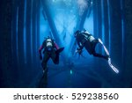 Two Divers On Oil Rig With Sea...