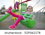 Happy Little Girl Is Swinging At Playground - stock photo