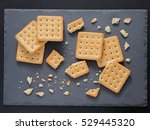 Small photo of Square crackers with pieces and crumbs on slate gray background. Dry salt cracker cookies with fiber and dry spices. Top view or flat lay.