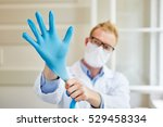 doctor putting gloves on as... | Shutterstock . vector #529458334