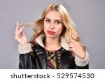 Small photo of Beautiful blonde woman in furl leather jacket posing in studio