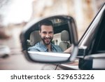 Driver in rear-view mirror. Confident young man smiling and looking at camera while driving a car - stock photo