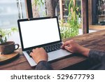 Stock photo mockup image of hands using laptop with blank white screen on vintage wooden table in cafe 529677793