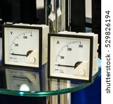 Small photo of The ammeter and voltmeter on the table with glass