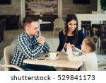 Family Enjoying Tea In Cafe...