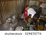 Small photo of BOR, SOUTH SUDAN, FEBRUARY 26, 2013: A woman cooks using traditional methods over a small charcoal oven in South Sudan. Charcoal is the only method of cooking in this region.