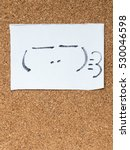 Small photo of The series of Japanese emoticons called Kaomoji on the cork board, smug