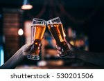 Stock photo two friends toasting with glasses of light beer at the pub beautiful background of the oktoberfest 530201506