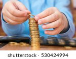 Small photo of Child amassed a large pile of gold coins, close-up