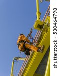 Small photo of Man working overboard. Abseiler climbing and hanging at the edge of oil and gas rig platform in the middle of sea.