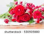 Stock photo bouquet of red roses on wooden table 530505880