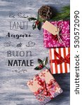 Small photo of high-angle shot of some cozy christmas gifts on a rustic wooden surface and the text text tanti auguri di buon natale, merry christmas written in italian