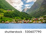 A lots of little colorful traditional Norwegian houses near the sea with green forest on mountains on background and blue sky with dark clouds, Sognefjord, Norway - stock photo