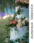 Small photo of White and pink roses beautify artificial blue wedding cake