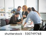 Small photo of Business people showing team work while working in board room in office interior. People helping one of their colleague to finish new business plan. Business concept. Team work.
