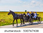 Small photo of Strasburg, PA - June 19, 2016: An Amish family riding in an open black wagon on a county road in Lancaster County, PA.