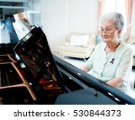 Happy Elderly Woman Pianist...