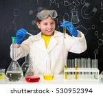 Small photo of schoolgirl in white gown doing experiments with liquids in chemistry lab