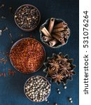 Small photo of Various spices - cinnamon, star anise, cloves, saffron, allspice in a bowl on a dark background