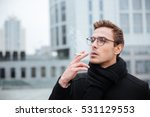 Cool Business man in glasses and warm clothes smoking cigarette on the street