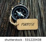 Small photo of PURPOSE inscription written on paper tag, compass on old wooden background.
