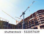 Small photo of High building under construction. Side with cranes against blue sky with sun glare.