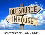 Small photo of Outsource, inhouse - wooden signpost
