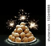 Small photo of Oliebollen (Dutch doughnuts) and fireworks, traditional Dutch pastry for New Year's Eve