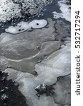 Small photo of Natural design - line and shape made of frozen water in small puddle. Ornamentation of ice.