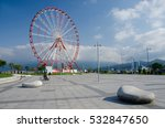 Small photo of Ferris wheel on the Batumi seafront with Caucasus mountains on the background, blue sky and stone-shaped benches,Georgia,Adzharia