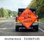 Small photo of ROAD WORK AHEAD attached to rear of utility truck.