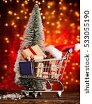 Small photo of Shopping cart for x mas season with cute little christmas hats and x-mas tree