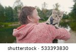 Stock photo woman shows the british shorthair tabby cat near forest river outdoor 533393830