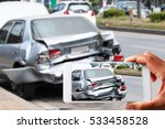 Small photo of Close up hand holding smartphone and view photo of car accident