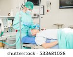 Small photo of Portrait of a male anesthesiologist administering a sedative to a patient before surgery