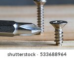 Small photo of Closeup of a screw screwed into wooden plank.