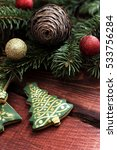 Small photo of Green fondant christmas tree cookies with golden decoration on a wooden table with fir cone and a twig