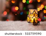 decorative house standing in the snow under the Christmas tree - stock photo