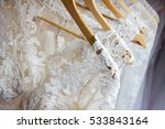 Wedding dresses hanging on a hanger. Fashion look. Interior of bridal salon.