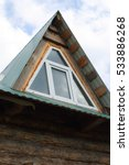 Small photo of Triangular skylight of an attic of a village log house under construction against a cloudy sky