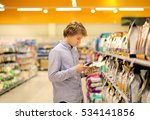 Stock photo  man shopping in supermarket reading product information using smarthone pet food 534141856