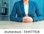 Small photo of Business negotiation skills with female executive sitting at office desk with confident pose and hands crossed, body language for determination and willpower