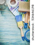 Small photo of Set of paint cans brushes color sampler adhesive tape on wooden board.