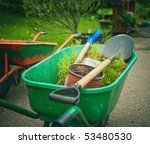 Green wheelbarrow standing in the garden - stock photo