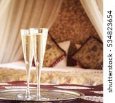 Small photo of Two champagne glasses with oriental canopy bed at the background. Silver tray. Romantic concept. Valentines background. Arabian nights ambiance. Square, glasses on left side, more defined background