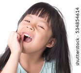 Small photo of Cute young four year old child holding her tooth which may be loose or aching