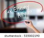 Small photo of Woman Hand Writing Enemy - Ally with a marker over transparent board. Isolated on Office. Business concept. Stock Photo