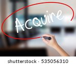 Small photo of Woman Hand Writing Acquire with a marker over transparent board. Isolated on Office. Business concept. Stock Photo