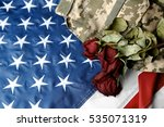 Dried roses and military uniform on American national flag. Veterans day concept